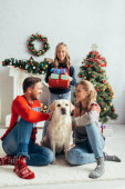 joyful parents in sweaters cuddling labrador near daughter with presents and decorated christmas tree