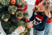 happy girl decorating christmas tree with parents at home