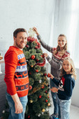 happy girl decorating christmas tree with joyful parents at home