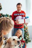 žena mazlení pes poblíž dítě a manžel s dárky na Vánoce