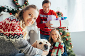 selective focus of happy woman cuddling dog near daughter and husband with gifts on christmas