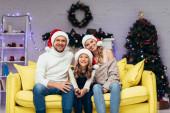Fotografie glückliche Familie mit Weihnachtsmützen blickt in dekorierte Wohnzimmer in die Kamera