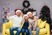 šťastná rodina v Santa klobouky držení jiskřičky v zdobeném obývacím pokoji