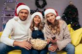 Fotografie glückliche Familie in Weihnachtsmützen blickt in die Kamera neben Schüssel mit Popcorn