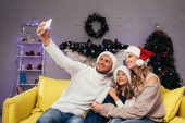 glückliche Familie in Weihnachtsmannmützen macht Selfie im dekorierten Wohnzimmer
