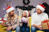 freudige Eltern mit Weihnachtsmützen, die Geschenke in der Hand halten und das Kind an Weihnachten im geschmückten Wohnzimmer anschauen
