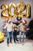 happy family in santa hats standing near presents and shiny balloons with 2021 numbers