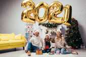 radostná rodina v Santa klobouky sedí v blízkosti dárky a lesklé balónky s čísly 2021