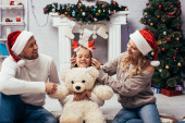 Photo mother wearing headband with reindeer horns on daughter with teddy bear near husband