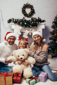 Photo happy kid in headband with reindeer horns holding teddy bear near presents and parents in santa hats