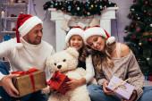 happy kid holding teddy bear near presents and parents in santa hats