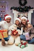 freudige Familie in Weihnachtsmützen mit Geschenken im geschmückten Wohnzimmer an Weihnachten