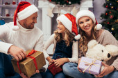 pleased family in santa hats holding gifts in decorated living room on christmas