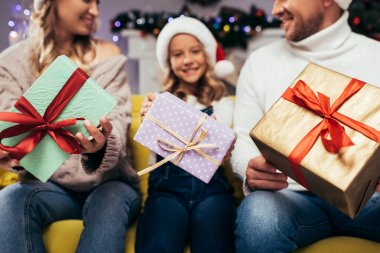 Christmas presents in hands of joyful family on blurred background stock vector