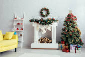 Vánoční stromek, věnec, punčochy a krb ve zdobeném obývacím pokoji
