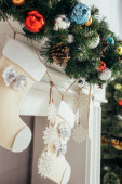 barevné koule a šišky borovice na jedli v blízkosti vánoční punčochy a krb
