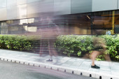 Photo motion blur of people walking on urban street near modern building