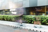 Photo motion blur of people walking on street near modern building