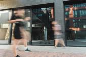 Bürger gehen auf Straße in der Nähe von Gebäuden, lange Belichtungszeit
