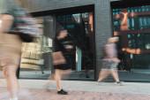 citizens walking on modern street near building, motion blur