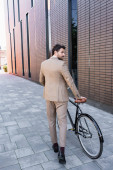 Photo full length of bearded businessman in suit walking with bike and looking away near building
