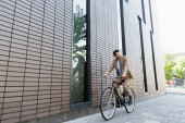 full length of businessman in suit riding bicycle and looking away near building