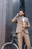 alacsony látószögű kilátás vidám üzletember beszél okostelefon és gazdaság papír pohár közel kerékpár és épület