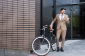 full length of smiling businessman holding smartphone and coffee to go near bicycle while standing near building
