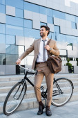 full length of cheerful businessman in wireless earphones standing near bicycle