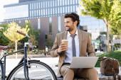 šťastný obchodník v obleku pomocí notebooku a drží papírový kelímek při sezení na lavičce v blízkosti kola