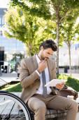 zamyšlený podnikatel v obleku drží digitální tablet, zatímco sedí na lavičce