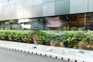 Long exposure of people walking on urban street near modern building stock vector