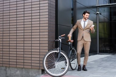 Full length of smiling businessman holding smartphone and coffee to go near bicycle while standing near building stock vector