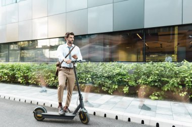 Motion blur of businessman holding smartphone while standing near e-scooter, plants and building stock vector