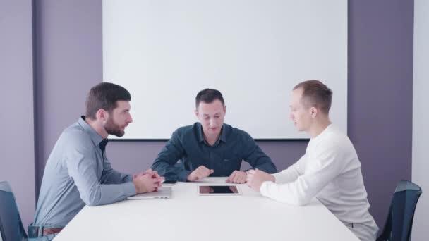 mladý podnikatel přijde na dva středního věku manažeři firem pro prezentaci jeho podnikatelský záměr při spuštění na obrazovku tabletu v zasedací místnosti 4k natáčení
