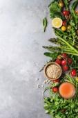 Rozmanitost zdravé vegetariánské stravování potravinových složek. Zelený chřest, rajčata, byliny, ořechy, kukuřice, pšenice, pampeliška listy, sklenice šťávy Šedá textura pozadí. Pohled shora, kopie prostor