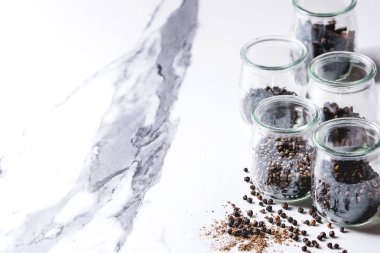 Variety of different black peppers allspice, pimento, long pepper, monks pepper, peppercorns and ground powder in glass jars on white marble kitchen table.