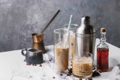 Fotografie Iced coffee cocktail or frappe with ice cubes and cream in different glasses with jezva, silver shaker, bottle of rum, coffee beans around on white marble table with grey concrete wall at background.