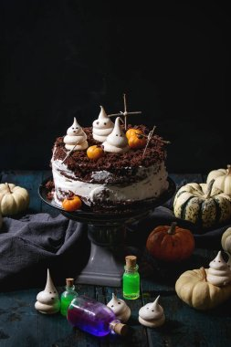 Halloween sweet table with cemetery chocolate cake, marzipan and decorative pumpkins, meringue ghosts, poison's bottles over black wooden table.