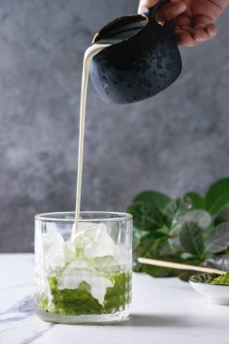Cream pouring from jug to matcha green tea iced latte or cocktail in glass, with ice cubes, matcha powder on white marble table, decorated by green branches. Grey wall at background