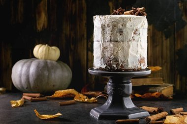 Autumn homemade white naked cake decorated by cinnamon sticks and anise on cake stand with yellow leaves and decorative pumpkins above on black table. Dark rustic style.