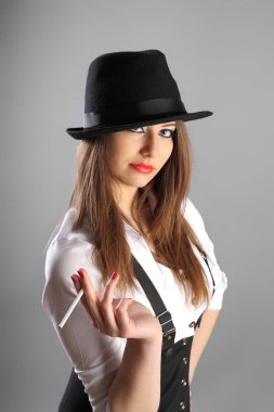 beautiful young woman in hat smoking cigarette in studio grey background