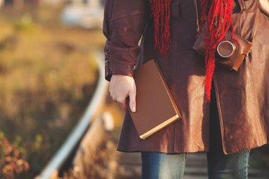 Young girl in leather coat with book walking along railroad in sunshine, sunrise