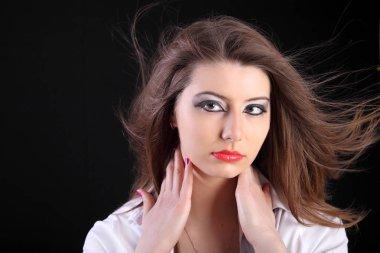 Beautiful brunette girl with studio fan wind on black background