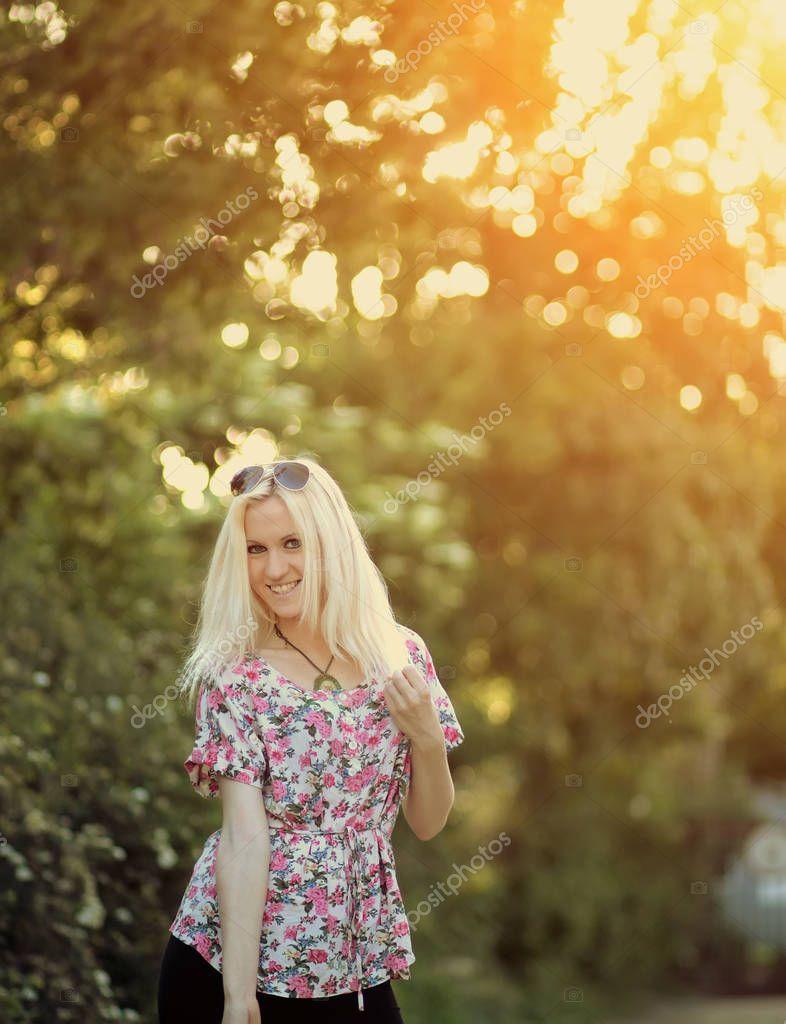 Spring woman in summer dress walking in green park enjoying the sun
