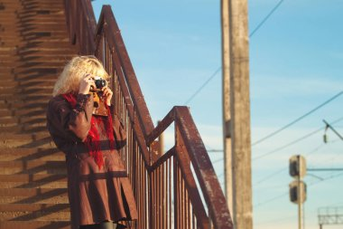 Young girl in leather coat with camera make photo on stairs bridge in sunshine, sunrise