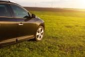 Neznámé vozidlo auto na trávě v oboru na letní západ slunce