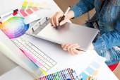 junge Künstlerin in Jeansjacke zeichnet im Büro etwas auf Grafik-Tablet