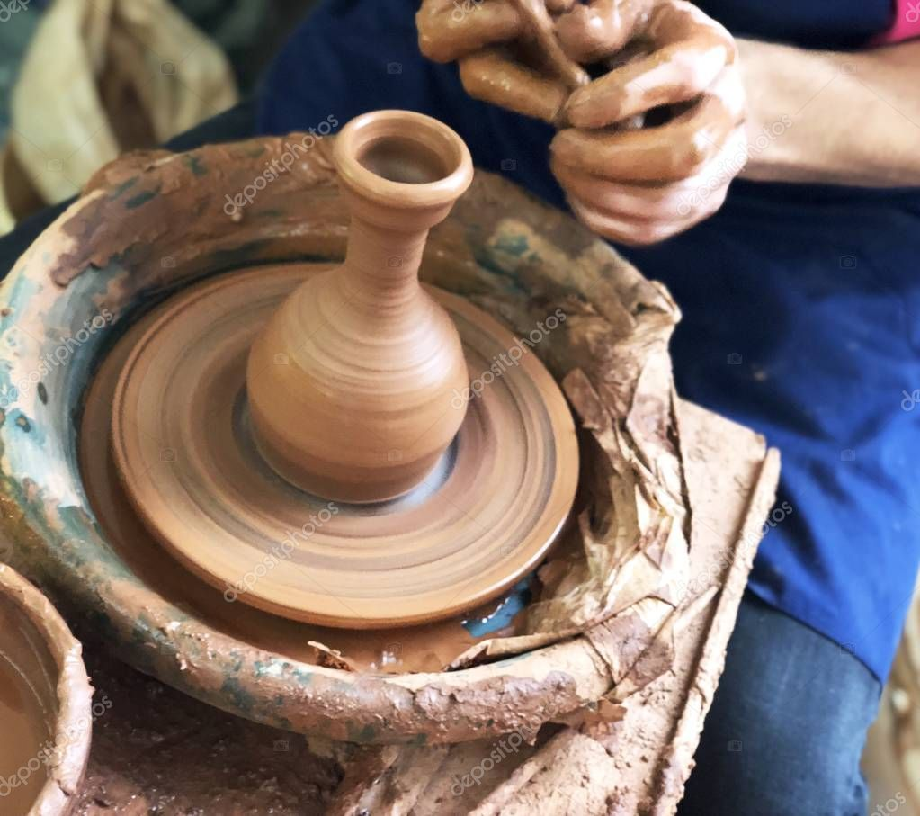 The hands of the Potter who makes the dishes from brown clay, the process of pottery craft