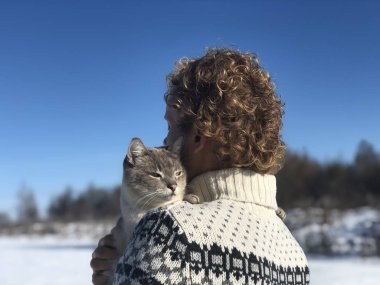 blue-eyed gray-white Siamese cat hugs with smile, love, and devotion the blonde curly-haired guy's shoulder. The cat was lost outside on a clear Sunny winter day and is now found by its owner